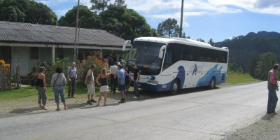bus stopped by roadway stand.